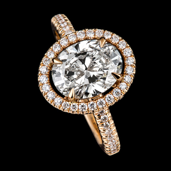 Boutique collection - Ariel oval cut diamond set in a rose gold and diamond halo mount with diamond set shoulders